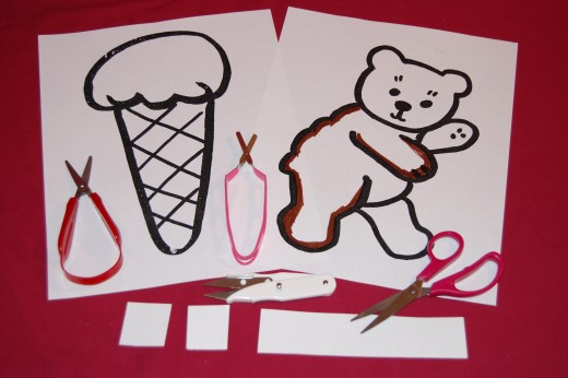 Try helping child cut narrow strips of paper or card stock