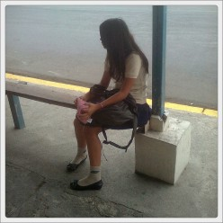 Loneliness defined. A poor girl looking  down a walkway that no one will be walking to see her.