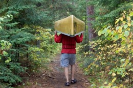 A man carrying a canoe in the Northwoods of the Minnesota  in the Minnesota Boundary Waters Canoe Area Wildnerness