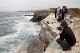 A group of people view the Pacific Ocean from a rocky cliff along Coast Dairies, CA during the Sand Hill Bluff Dedication.