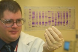 A chemist reads a DNA profile: a biochemist with some laboratory experience could command over $55,000 per year (on average).