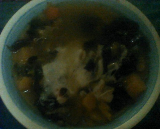 A bowl of Hearty Harvest Vegetable Soup garnished with shredded cheese.