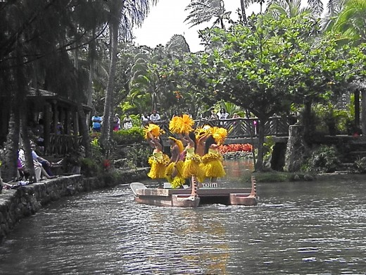 The Parade of Canoes takes place every afternoon at the Polynesian Cultural Center.  Tahitian dancers perform on a floating canoe in this photo.