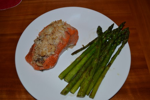 A delicious seafood dinner with salmon stuffed with crab and sauteed Asparagus
