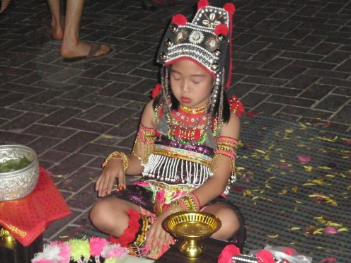 Thai girl dressed in traditional religious-related attire. Street photography at Chang Mai Night Bazaar, Thailand.