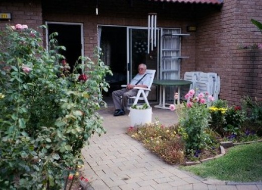 Dad as I want to remember him - enjoying the sunshine on his porch surrounded by flowers