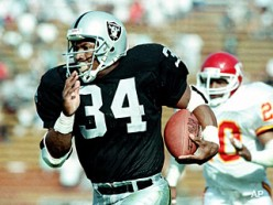 All-World Athlete Bo Jackson rushing the ball for the Oakland Raiders