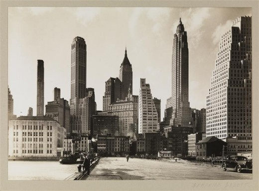 Title: Manhattan I Date: March 26, 1936 Comments: View of the contrast of 19th century dockside buildings and 20th century skyscrapers taken from Pier 11 on the East River, between Old Slip and Wall Street.  The four tallest buildings are (from left