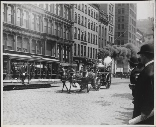 Title: [Fire engine on lower Broadway] Date: 1900 Comments: View of a horse-drawn fire truck on lower Boadway. A crowd watches from both sides of the street.