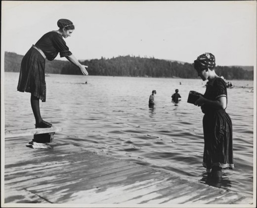 Title: [Woman standing a lake, photographing another woman who is perched to dive] Date: 1900 Comments: Those were the swimwear back in the day .