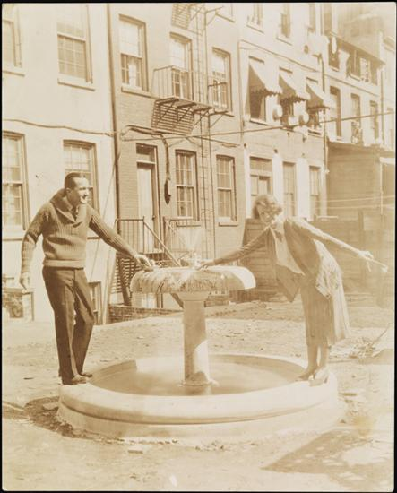 Title: [Couple standing near fountain in Greenwich Village.] Date: 1915