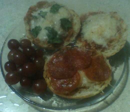 A plate of Enchanting English Muffin Pizzas, served with a bunch of grapes