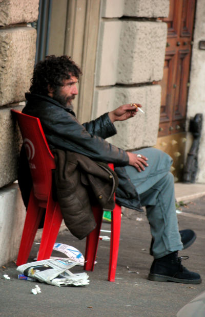 Homeless man relaxing for a smoke.