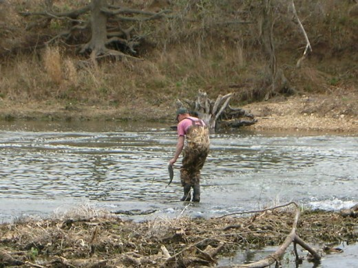 Dad wades out into the river to catch larger fish, while I fish from a sandber.