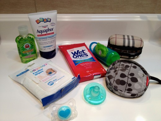 """Diaper Bag """"Extras"""" - antibacterial wipes & lotion, pacifier holders & wipes, Aquaphor can double as diaper cream & hand lotion, and scented diaper disposal bags."""