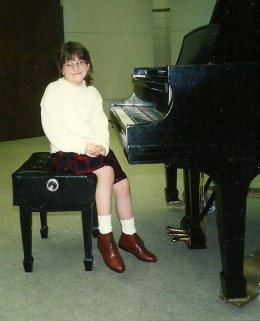My daughter after her first piano recital where she won a blue ribbon for her efforts.  Nearly 30 children of all ages, from 5 to 17, participated.