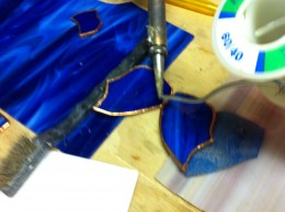 Applying solder to adhere the two pieces of glass together.
