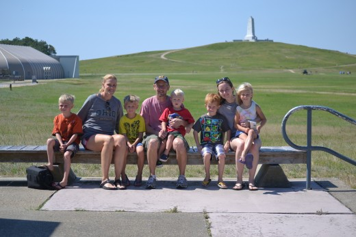 Our family outside the visitor center with the Wright Brothers National Memorial in the background