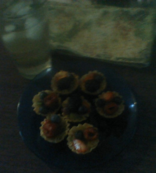 Mini fruit tarts on a blue plate, with a tall glass of iced mano chamomile sun tea next to it.