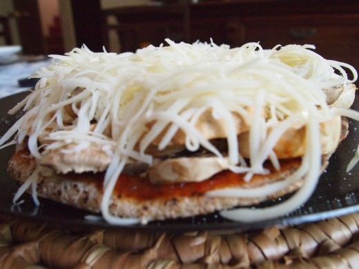Top the pita pizza with grated mozzarella cheese. Notice how tall the layering gets. The big champignon layer will add great juiciness and flavor.