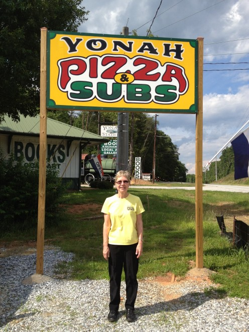 The owner, Debbie Bewsher, standing under the Yonah Pizza & Subs sign.