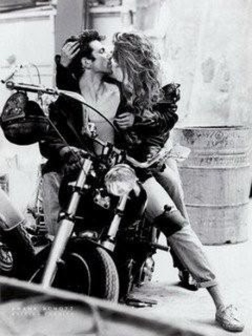 A biker kisses his date after taking her for a wild ride.