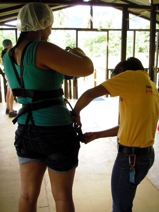 Hotwire Rides guides check harnesses for safety before we zip line above the canopy at Morne Coubaril Estate..