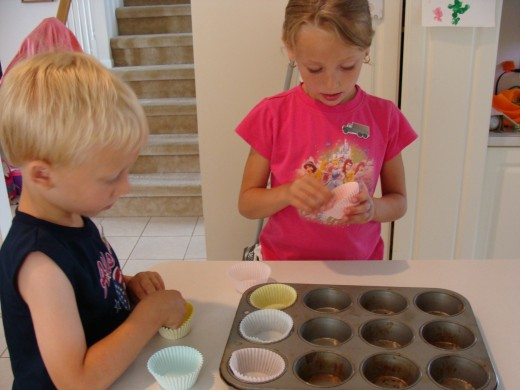 Grace and Alex line the muffin pan with paper liners.
