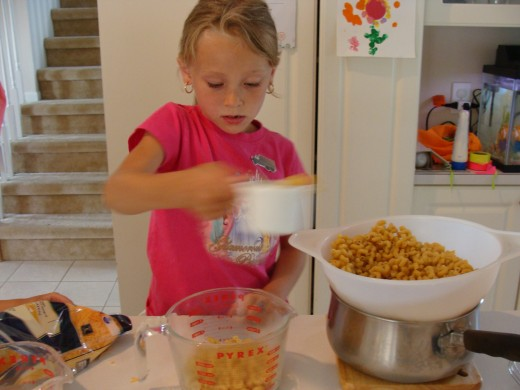 Grace carefully measures the cooked pasta.
