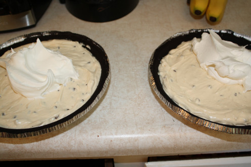 Pie mixture in pie shell, putting layer of cool whip on top