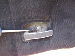 A screwdriver points to the screw that holds the door handle back plate on. (The back plate has been removed in this photo.)