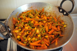 The third and final part of the cooked rice is to be mixed with the cooked vegetables.