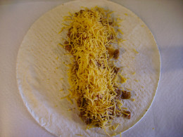 Layer first the ground beef/bean mixture, then the salsa, and finish with the shredded cheese.