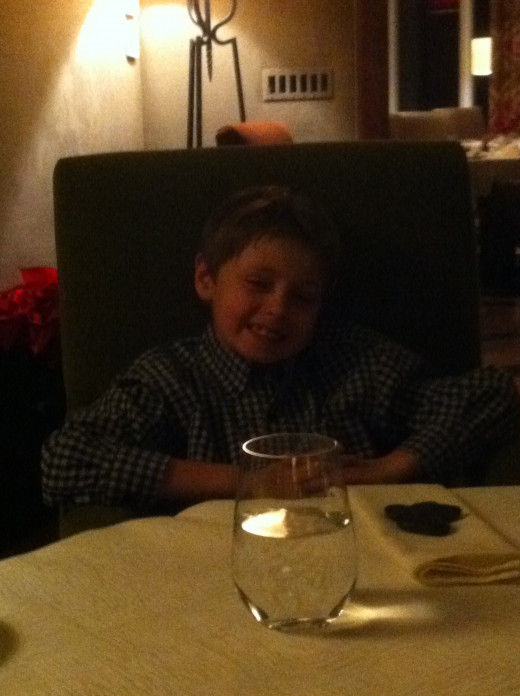 Our oldest son, enjoying a fancy dinner for New Year's Eve despite the collared shirt and cloth napkin.