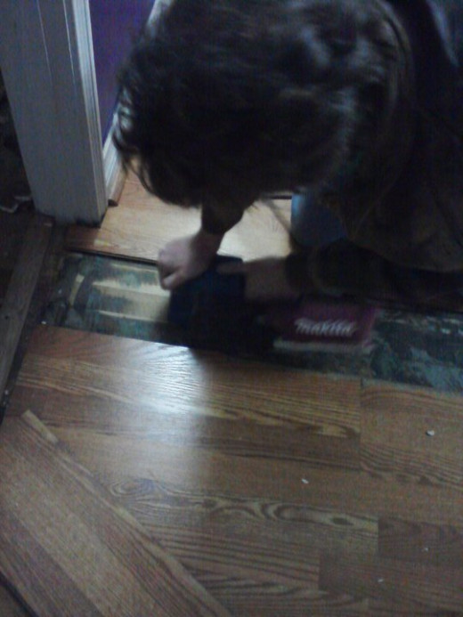 Here's your author seeing what a tiny belt sander will do to the goop on the floor under the laminate.