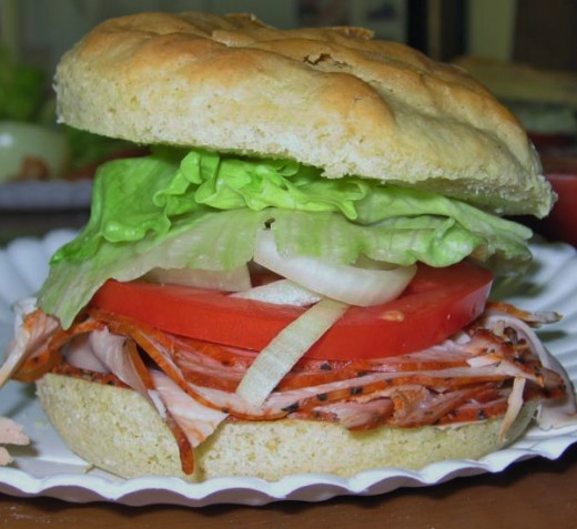 The turkey pastrami is served on a gluten-free onion roll with lettuce, onion and tomato. The rolls are available for order.