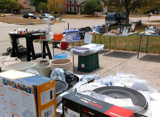 A plastic storage container turned upside down or saw horses can be used as tables for a yard sale.