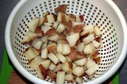 Drain cubed potatoes after boiling.