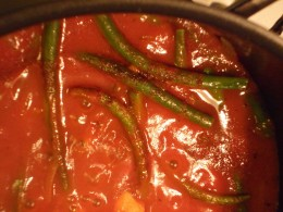 Green beans and hamburger with a base of tomato sauce.  It would be a delicious recipe even without the cheddar cheese cubes in each fluffy white dumpling!