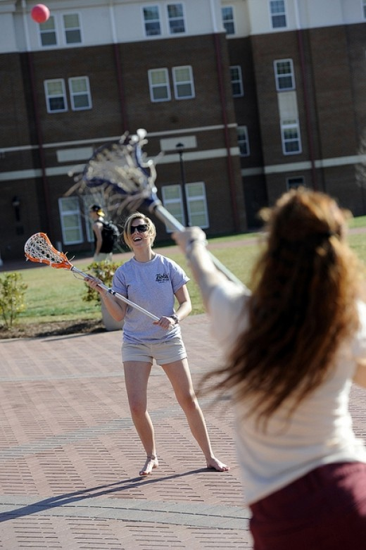 Tossing the ball lacrosse style by the fountain