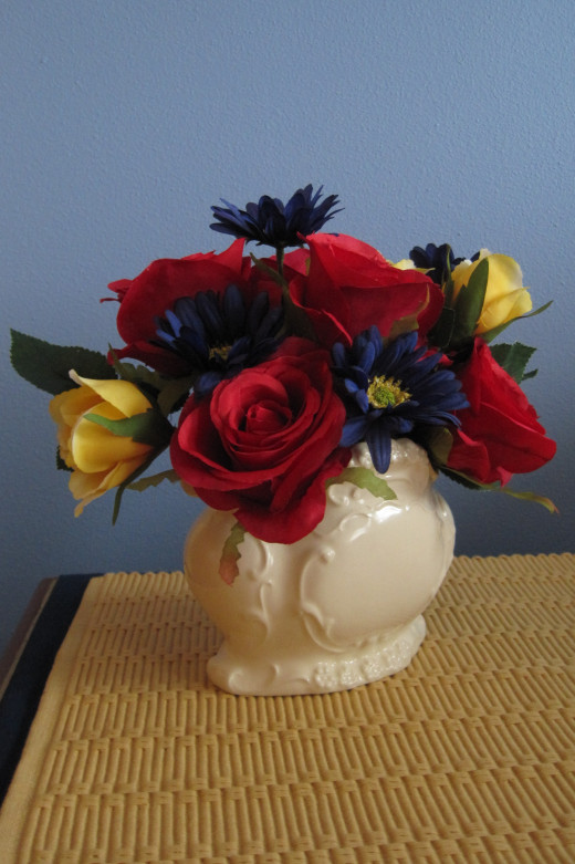 White vintage vase with yellow, red and blue flowers.