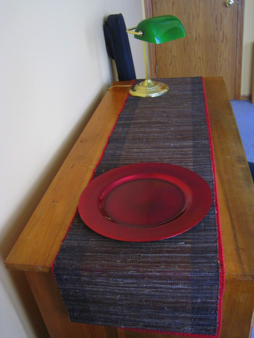 Desk with two runners, lamp and charger plate.