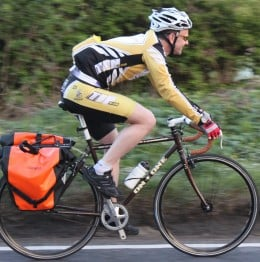 A commuter cyclist riding an On One Pompino bike with panniers on their way home from work