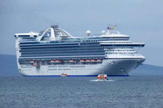 Tenders/life boats are bringing passengers back to the Caribbean Princess cruise ship in Kirkwall harbour in the Orkney Islands, Scotland UK in 2012. Note that the tenders are covered. Also most of the rooms on the ship have balconies.