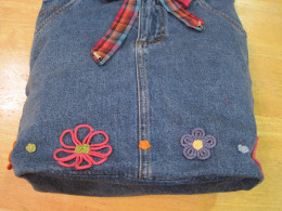 I did not want to lose any of the very retro embroidery so I cut nothing off of this skirt.  I simply used a piece of denim that closely matched the skirt's fabric to cut an oval shape to fit into the bottom edge.  It was a simple process.