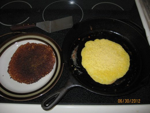 Half done pancake, with a finished product on a plate next to it.