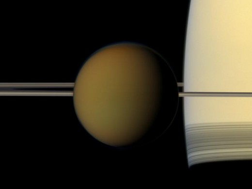 Cassini's photo of Saturn's methane-smog moon Titan (3200 miles across, about half the size of Earth) against the limb of Saturn. The rings' shadows against the fuzzy planet are always beautiful.