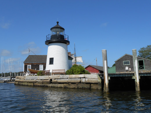 The Mystic Seaport lighthouse on the banks of the Mystic River, surrounded by replicas of buildings in 1876.