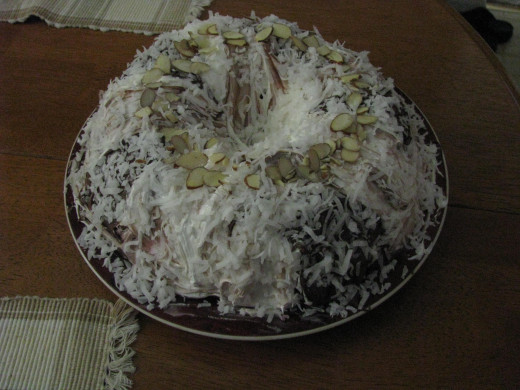 9.  This was supreme.... Alternated Whipped Vanilla with milk chocolate sprinkled with sweetened Coconut and top middle dotted with sliced almond- Center Black cherry icing and whipped cream mixed together.