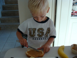 Alex very carefully spreads the peanut butter on his sandwich.